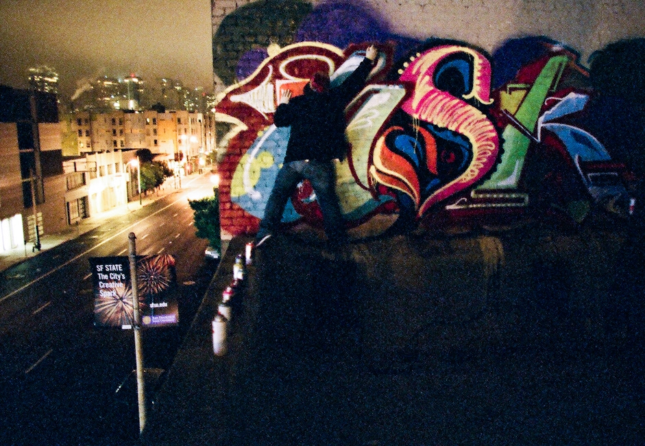 A graffiti writer on a rooftop in the city